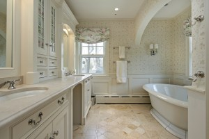 Master Bathroom Remodel with Double Vanity and Pedestal Tub. Stone Tiles, Stone Countertops, Beaded Inset Cabinets, Wallpaper and Painted Wood Wainscot Finish the Room