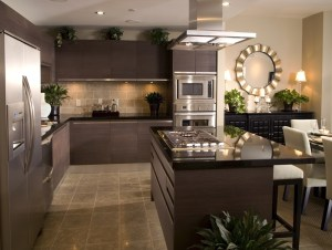 Kitchen Remodel with Modern Dark Slab Door Cabinetry, Black Engineered Stone Countertops, Full Height Stone Tile Backsplash and Stone Tile Flooring with Stainless Steel Appliances Open to the Dining Room with an Island between