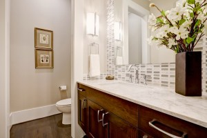 Whole House Remodel with Bathroom, including Stained Wood Vanity with White Stone Countertop, Full Height Glass Mosaic Tile Backsplash and Toilet tucked around Full Height Wall Beyond