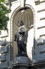A alegoria do Comércio porta o caduceu, atributo típico do deus mitológico Mercúrio.