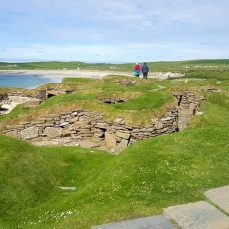 prehistoric village skara brae in the sun beach in background