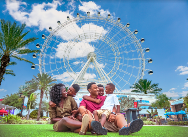The Wheel ICON Park discounts: image of a family of four in front of The Wheel ride at ICON Park in Orlando