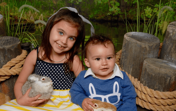 Easter Orlando 2021: image of a girl and boy holding bunnies in the Easter Bunny Garden Experience at ICON Park off I-Drive in Orlando