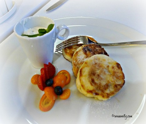 Soft cheese pancakes with kumquats, strawberries and sour cream