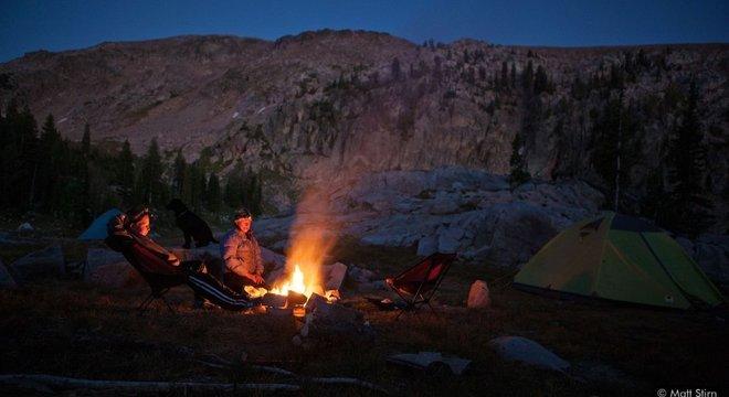 Após um longo dia nas montanhas, pesquisadores relaxam em volta da fogueira