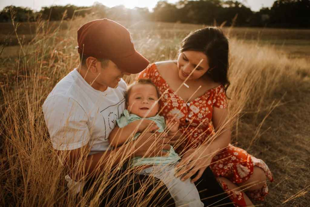 Couple with a baby sitting in the grass
