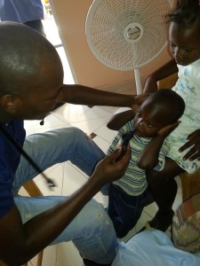Dr. Peter treating children while at the Ephraim Orphanage