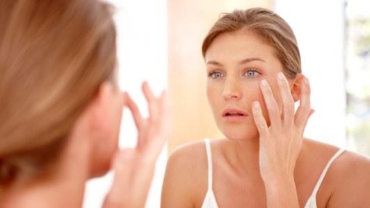Woman looking in mirror, transepidermal water loss