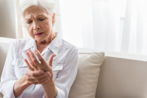 lady sitting on couch experiencing hand pain