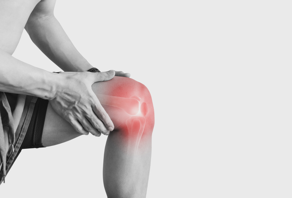 man experiencing knee pain. knee highlighted in red for pain