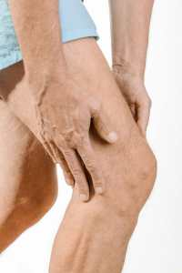 Hands gripping knee in pain due to meniscus tear