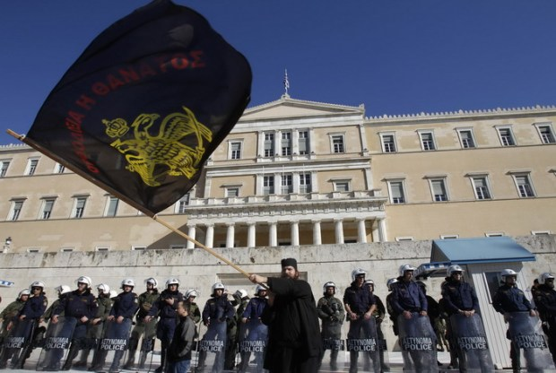 A monk waves a flag in front of riot police guarding the parliament during a rally in Athens