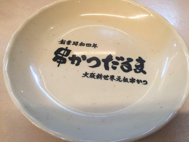 だるま北新地,串かつだるまのロゴが入った白いお皿がカウンター席に置かれている様子
