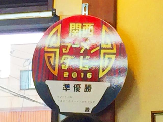 あいつのラーメン かたぐるま,店内の柱に関西ラーメンダービー2016の準優勝を証明する丸いポスターが貼られている