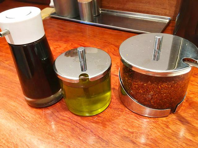 SHIBIRE-NOODLES 蝋燭屋,茶屋町あるこ,テーブルの上に3種類の調味料が並べられている,