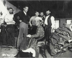 Niño de 12 años cosiendo en un taller clandestino. 1889. Jacob Riis