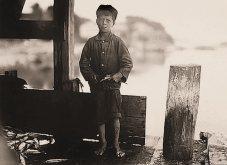 """Hiram Pulk, de 9 años, trabaja en una empresa conservera. """"No es muy rápido sólo 5 cajas al día. Le pagan unos 5 centavos de dólar por caja"""", dijo. Eastport, Maine. Lewis Hine"""