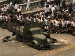 Scene from a Canadian embassy staff quarter at noon on 4 June 1989, three kilometres east of Tiananmen Square and several hours after the massacre. Soldiers are seated, waiting for orders beside their disabled truck and several corpses covered by coats. A little later, the soldiers departed and the bystanders set the truck ablaze. This same evening, the Canadians were evacuated after shooting erupted in the area. Source: John Morrison, an officer at the Canadian Embassy in Beijing.