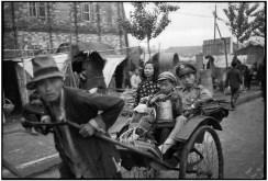 CHINA. Jiangsu. Nankin. Abril de 1949. Con sus pocas pertenencias apiladas en un carruaje, un soldado y un niño tratan de huir de la ciudad, justo por delante del Ejército comunista. En el fondo, las viviendas precarias albergan los miles de refugiados de la guerra civil.