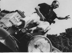 Der Fotograf Martin Munkacsi mit Kamera auf dem Dach eines Autos vor 1934