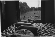 CANADA. Lambton County, Ontario. 1995. After his friend shaved his head, Moses TOWELL lies on a hand crocheted bedspread that his mother Ann made. His bedroom window faces the south pasture. You can hear the cows in the morning grazing by the window, or at night, moving in a herd. Moses shaved his head as it was the style at the time. Even country boys can be in style. Moses went away to camp this summer, bald head and all.