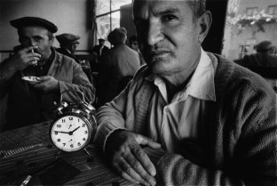 TURKEY. 1970. The workers of a local steel foundary have tea in a local teashop, the alarm clock indicates the time they must return to work.