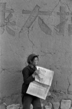 "CHINA. 1965. Farmer of the Henan. At the exit of the canteen, she reads ""The young China "". On the front page: "" successful Explosion of the second atom bomb ""."