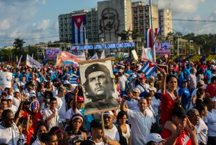 """Cubans file past, one holding a poster that depicts revolutionary hero Ernesto """"Che"""" Guevara, in the annual May Day parade at Revolution Square in Havana, Cuba, Tuesday, May 1, 2018. (AP Photo/Desmond Boylan)"""