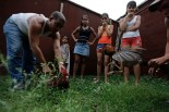 Youths watch their roosters fight during a training session in Havana June 25, 2012. REUTERS/Desmond Boylan (CUBA)