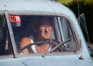 70-year-old Gilberto Ruiz sits at the wheel of his modified 1948 Ford in Havana July 12, 2012. Gilberto, who was unemployed, with a big family to support and his permit to use his car as a private-licensed taxi had expired, literally welded himself a new job and cut up his sedan turning it into a pick-up truck to work in the private transport bussiness. REUTERS/Desmond Boylan (CUBA)