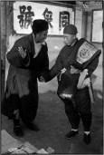 CHINA. Pekín. De diciembre de 1948. Un comerciante y un cliente se saludan. No hay ansiedad, es un cordial encuentro aunque la ciudad está sitiada por las tropas del Ejército Popular de Liberación. El plan del Kuomintang era huir en un plazo de ocho días. Pero incluso en la víspera de un evento tan dramática, los ciudadanos mantienen la calma.