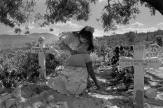 EL SALVADOR. San Salvador. 1991. A daughter comforts her mother who passed out while grieving at the grave of her son who was killed by government death squads. Some 70,000 persons died in the 12-year civil war.