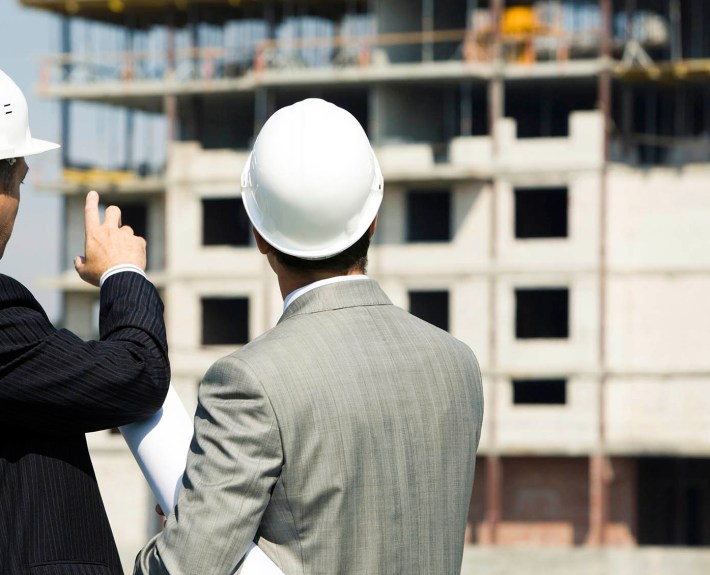 Photo of successful architect pointing to the building with foreman near by