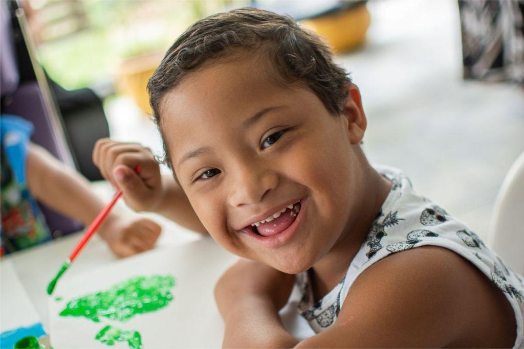 Pietro sorri enquanto pinta um desenho