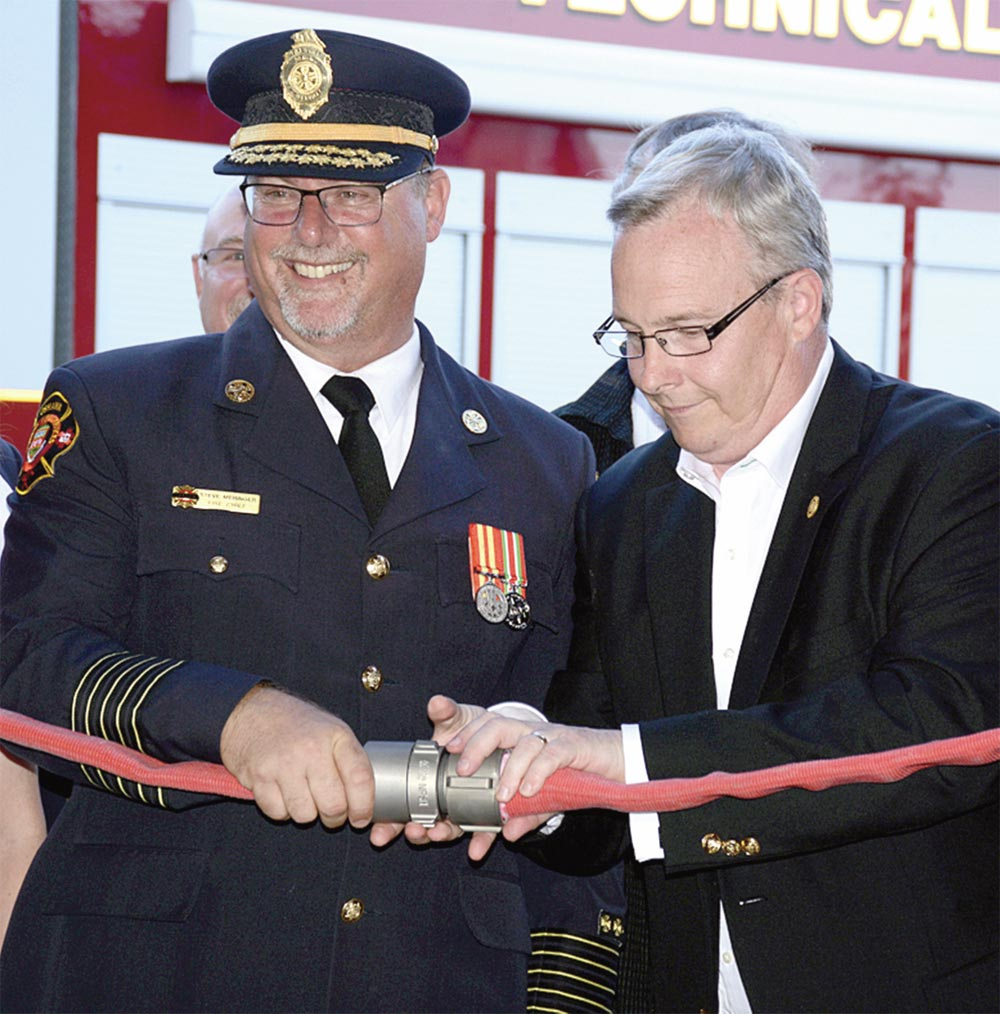 Fire Chief Steve Meringer and Mayor John Henry get ready to cut the ribbon - or rather, uncouple the fire hose - to mark the grand opening of Fire Hall 6. The new fire hall will serve the city's growing northern reaches.