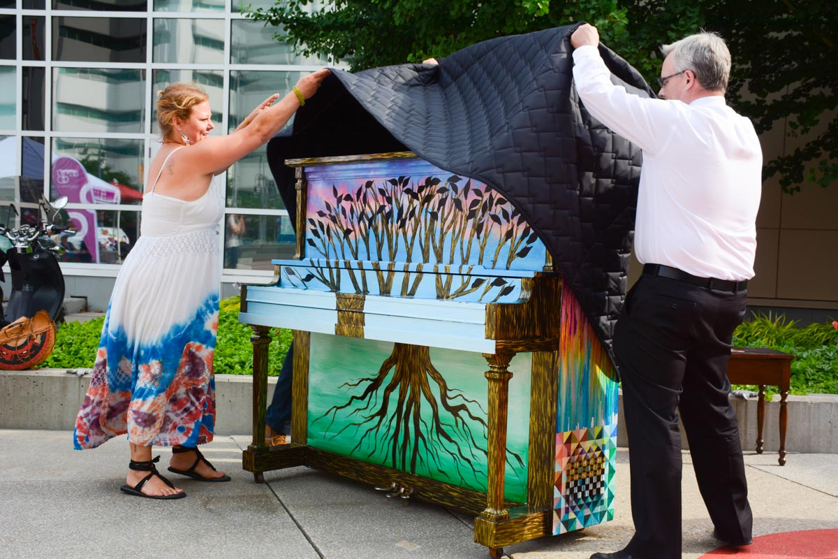 Artist Monique Ra Brant and Mayor John Henry lift the cover on the first piece of the 88 Keys project. Inspired by similar initiatives around the globe, the 88 Keys project will see three painted pianos placed throughout Oshawa, free to play and admire.