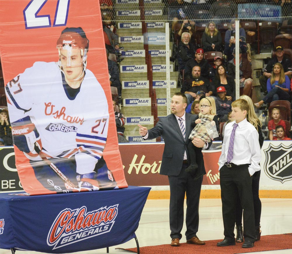 Marc Savard (left) stands with his family on the ice at the General Motors Centre on Oct. 2 as the banner displaying his retired No. 27 is hoisted into the rafters. Savard became the fifth player in the Generals' 80-year history of hockey to have his number retired in 80 seasons of hockey.