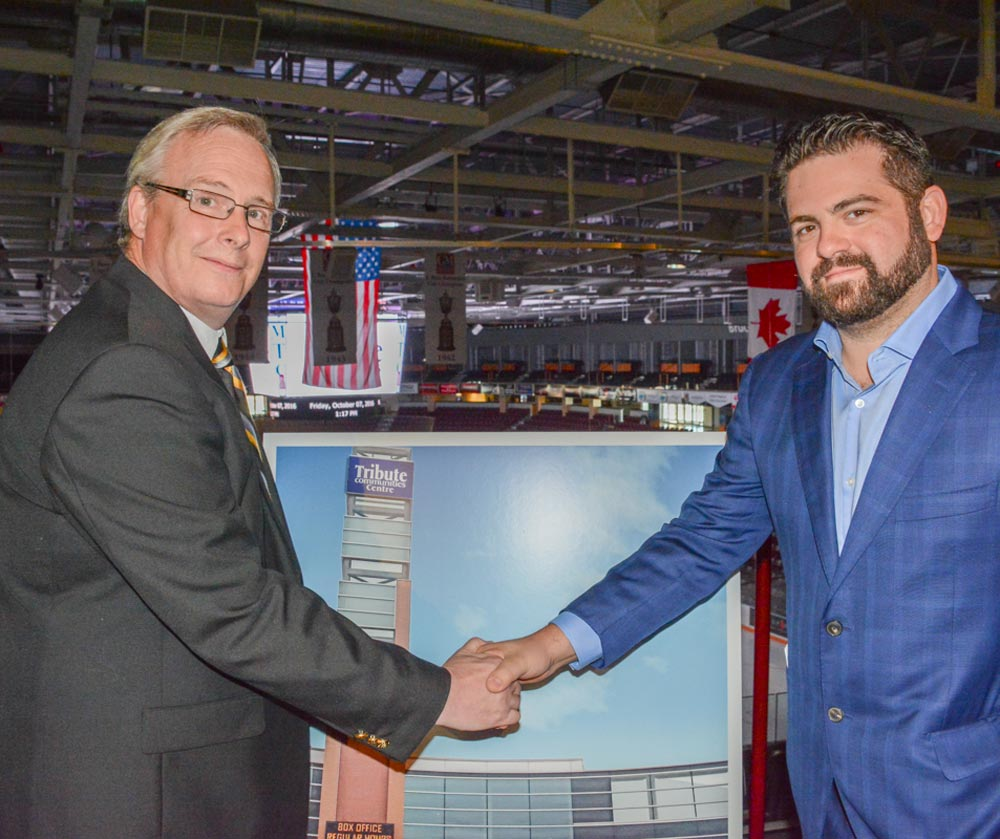 Mayor John Henry, left, and Steven Libfeld, the CEO of Tribute Communities, shake hands following the announcement that the developer will be taking over the naming rights of the soon-to-be former General Motors Centre as of Nov. 1.