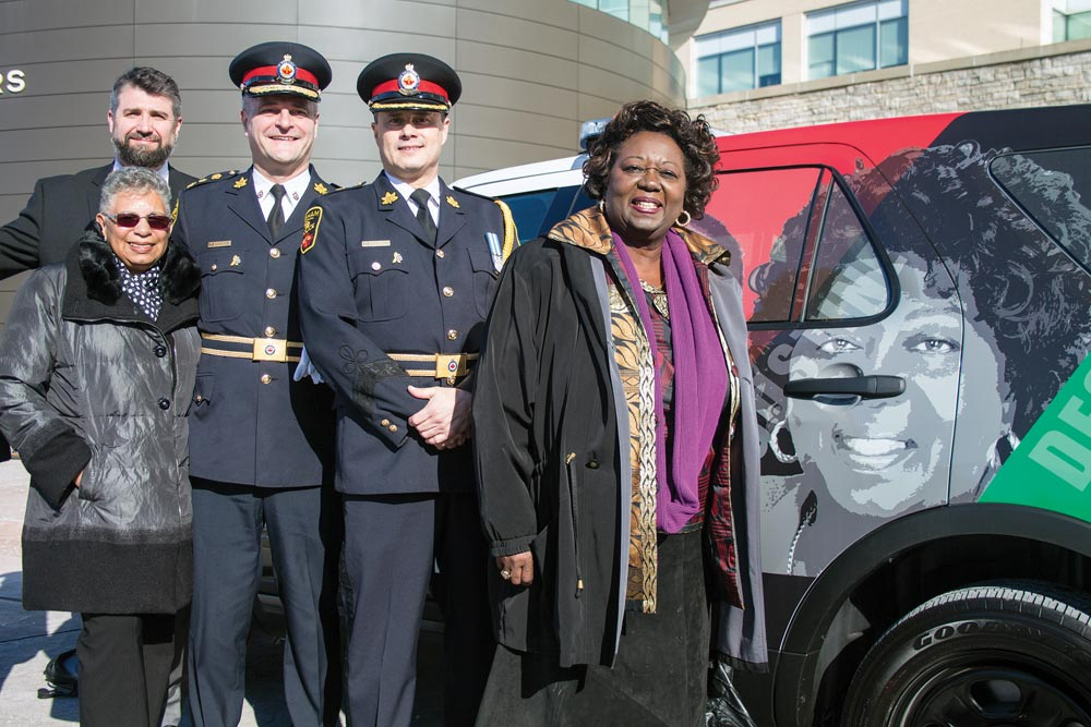 Jean Augustine, the driving force behind bringing Black History Month to Canada, joins Chief Paul Martin and Deputy Chief Chris Fernandes in front of a new DRPS cruiser honouring the accomplishments of black people in Canada and abroad, one of whom is Augustine herself. Augustine is one of six people featured on the vehicle.