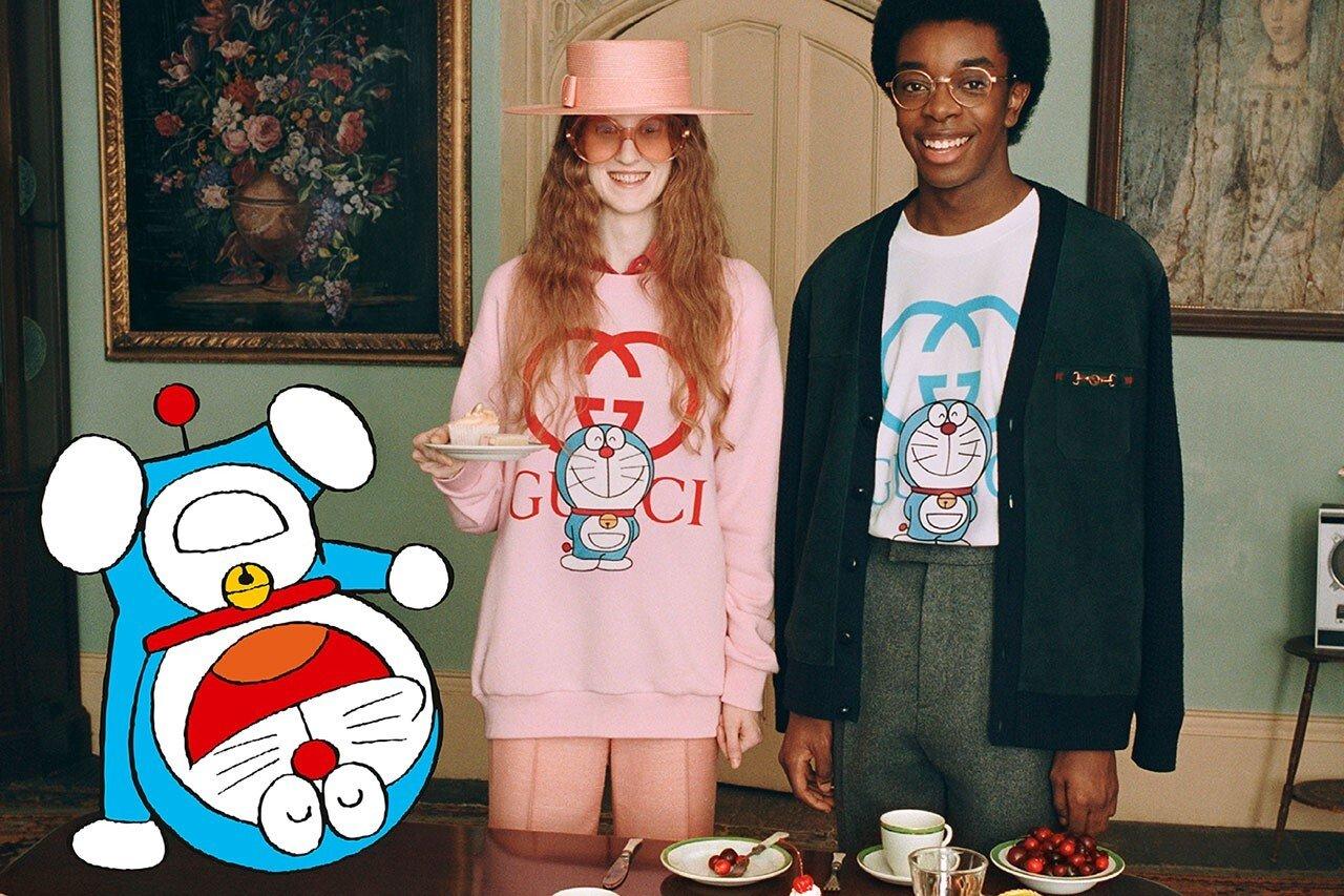 구찌와 도라에몽 콜라보레이션 컬렉션 화보이다. 도라에몽이 웃으며 물구나무 서는 모습이 보이고, 그 오른쪽에 한 여성과 남성이 도라에몽이 그려진 구찌 맨투맨을 입은 채 웃고 있다.