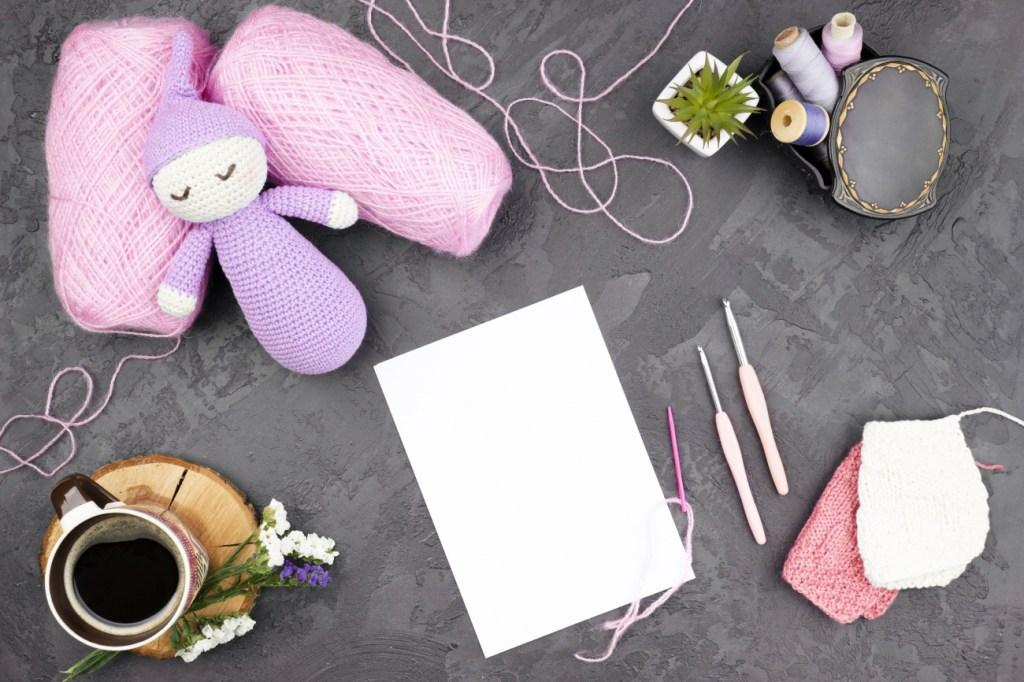 회색배경에 핑크색 뜨개질실이 두개 있으며 종이와 코바늘 장갑과 컵 그리고 반짓고리가 있는 사진이다.