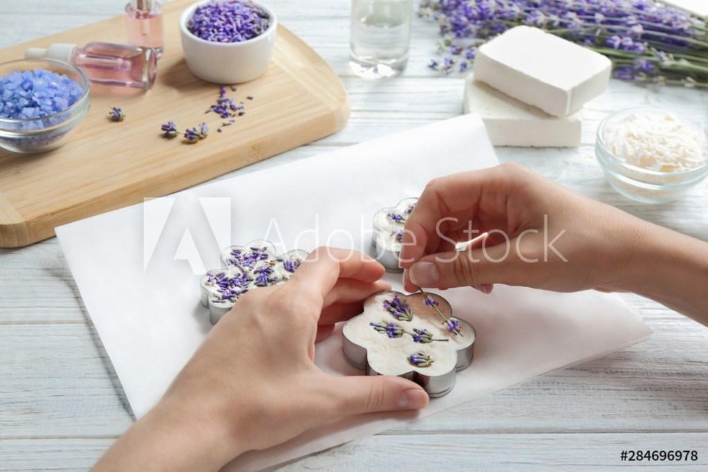 사람이 비누베이스가 들어있는 꽃모양 틀에 꽃을 데코하는 사진이다.