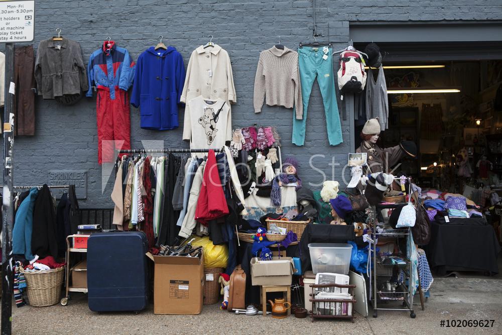 파란벽에 10벌의 옷과 가방이 걸려져 있으며 그 밖에 바닥에도 캐리어 등 자질구레한 물건들이 놓여있고 행거에 옷도 걸려있다.