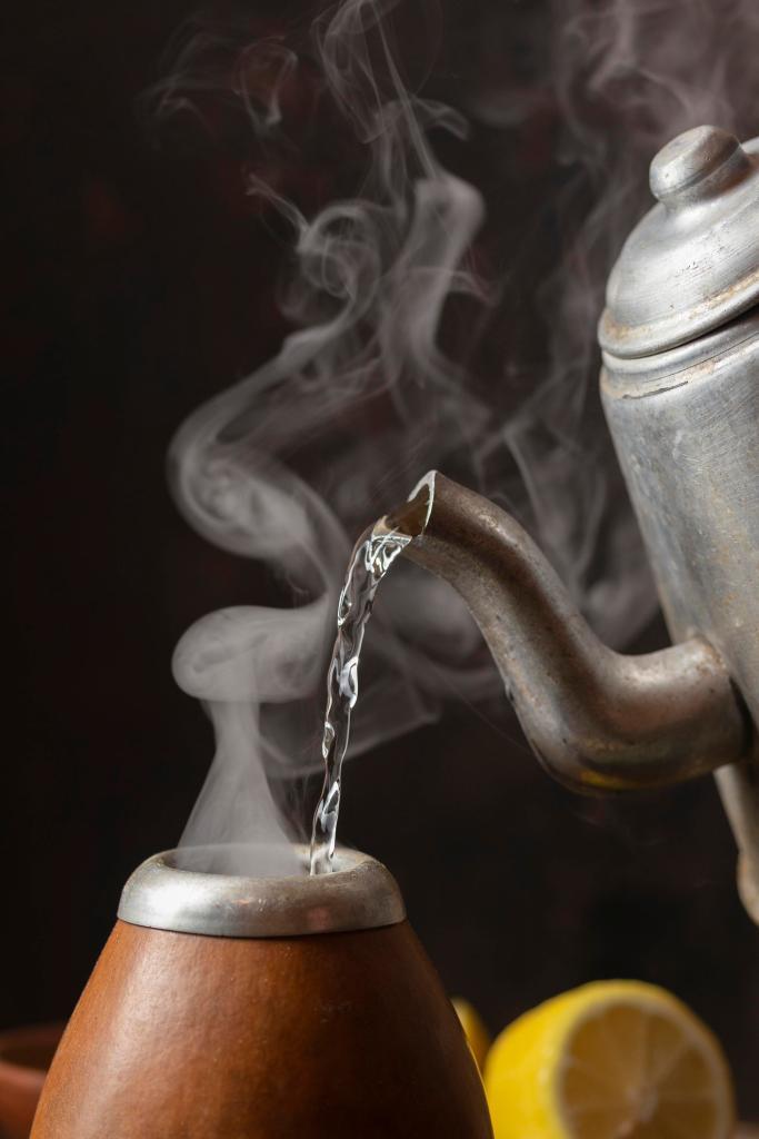 스테인리스 주전자로 겉면이 나무로 된 물통에 뜨거운 물을 담고있다.