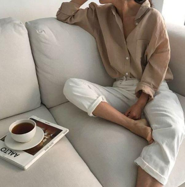 한 여자가 소파위에 베이지색 셔츠와 흰색 팬츠를 입고 차 한잔을 하고 있다