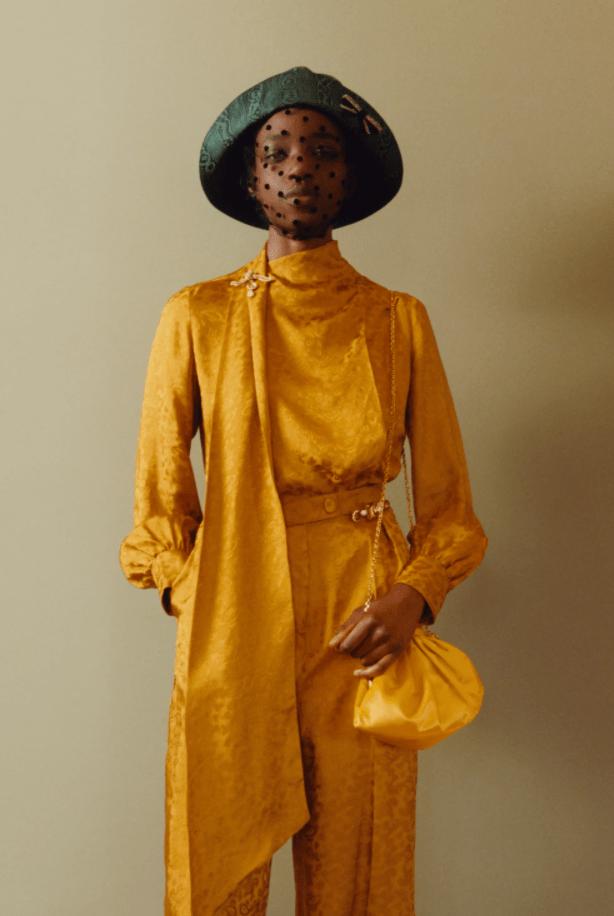 옐로우 탑과 팬츠의 조화 블라우스에는 스카프의 디테일이 더해졌다 그린 컬러의 고급스러운 모자도 포인트 얼굴에 착용한 베일의 도트 무늬는 독특함을 더해준다