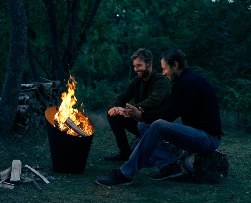 Photo of two men keeping warm next to the Morso fire pot