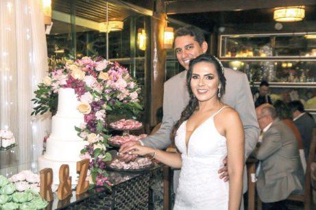 O casal, feliz, posa para fotos cortando o bolo