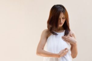 Woman checking for breast inflammation