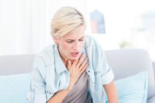 Pretty blonde woman having anxiety and breath difficulties in the living room